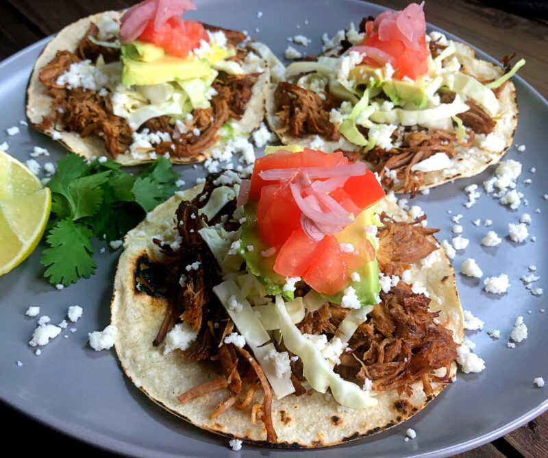 3 carnitas tacos with vegetable toppings
