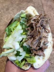 homemade pita bread cut in half and stuffed with instant pot kalua pork