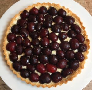 tart shell with cream and sliced cherries