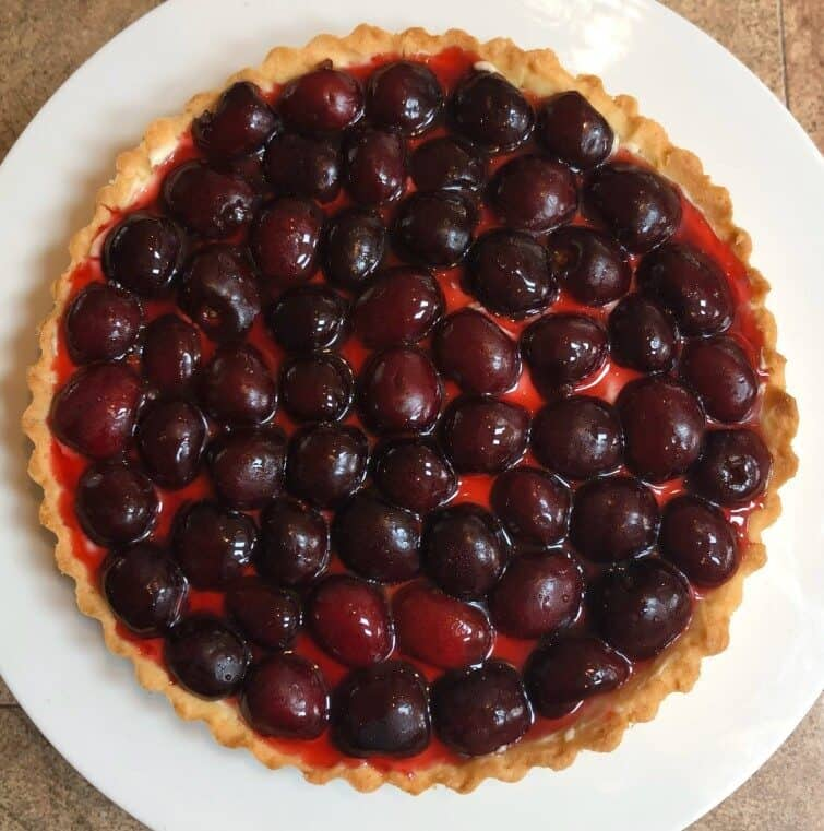 tart shell with cream, sliced cherries and cherry sauce