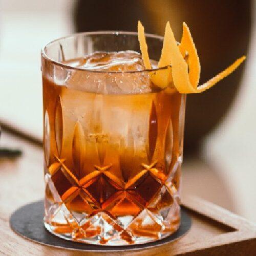 gin cocktail with orange peel garnish