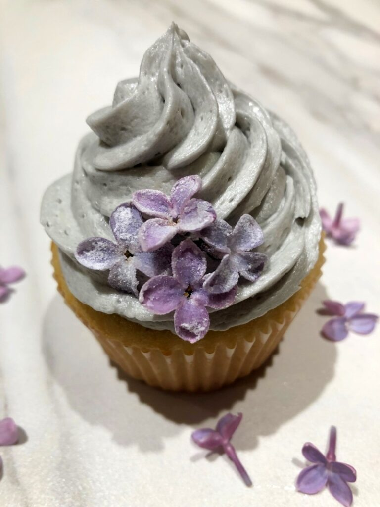 lilac cupcake with lilac buttercream frosting and candied lilac flowers on top