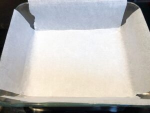 pan prepared with parchment for snickers bars