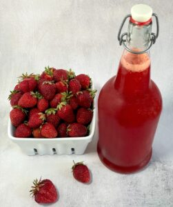 strawberry shrub in a flip top bottle next to fresh strawberries