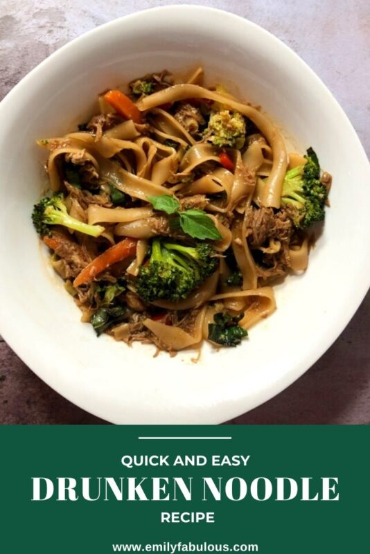 drunken noodles with fresh vegetables in a white bowl with a thai basil garnish