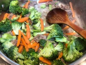 vegetables and kalua pork cooking in pan