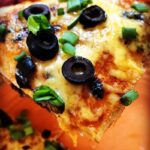 homemade mexican pizza slice with cheese, olives and green onions