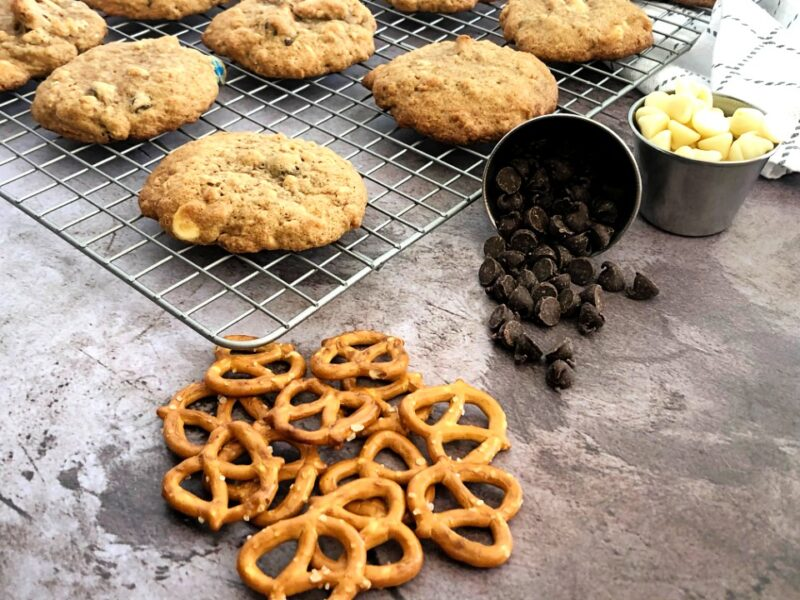 kitchen sink cookies on a cooling rack with pretzels and dark and white chocolate chips