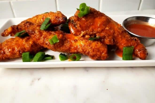 air fryer buffalo chicken tenders with green onion garnish and sauce