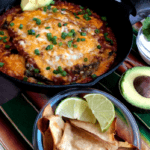 baked chile rellenos in a cast iron pan with chips, sour cream and avocado