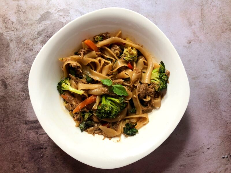 homemade drunken noodles in a white bowl with fresh vegetables and thai basil