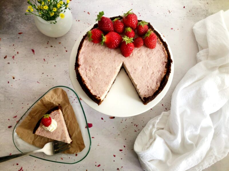 instant pot strawberry cheesecake on a cake stand with fresh strawberries on top and a slice of the cheesecake on a plate on the counter