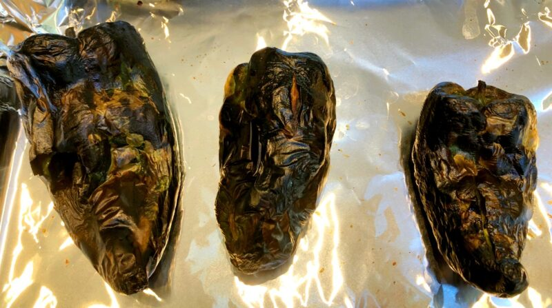 roasted poblano peppers on a baking sheet with tin foil