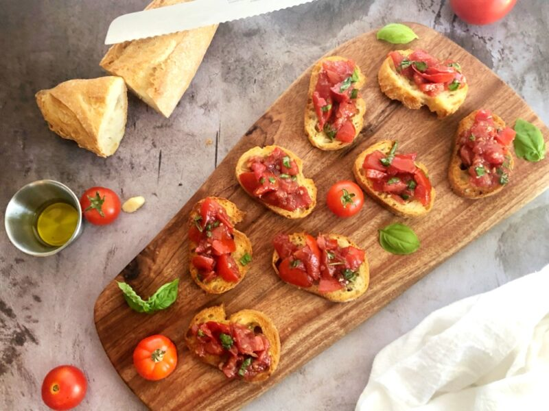air fryer bruschetta on a cutting board with tomatoes, basil, garlic and olive oil