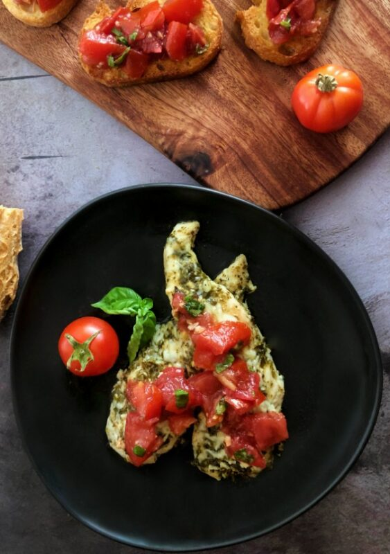 baked pesto chicken with bruschetta and bruschetta on bread