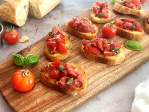 bruschetta on toasted bread on a cutting board
