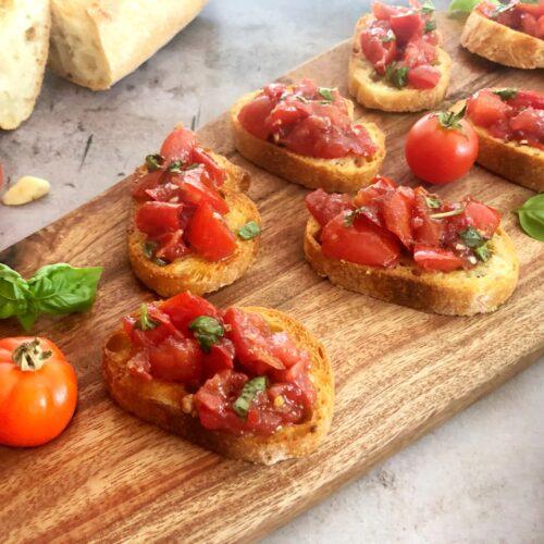 bruschetta on toasted bread on a cutting board