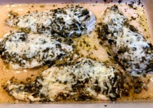 chicken with pesto and cheese in a baking dish