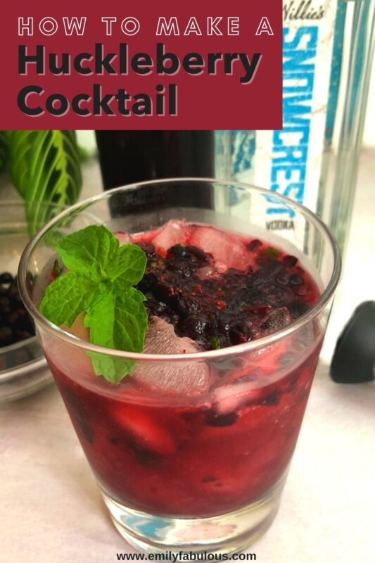 fresh huckleberry cocktail with mint and vodka bottle