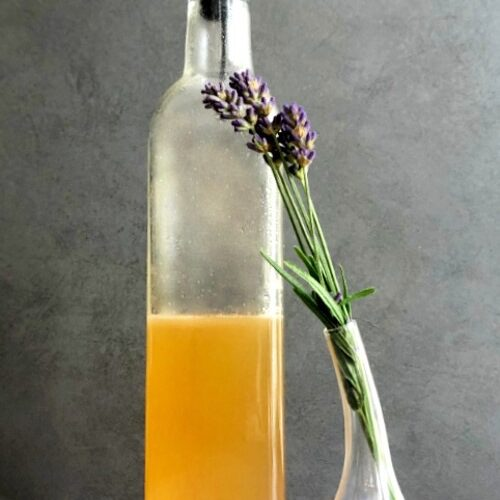 honey lavender syrup in a bottle with dried lavender buds in a vase