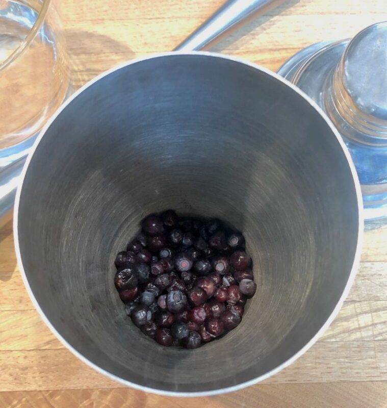 huckleberries in a cocktail shaker before muddling