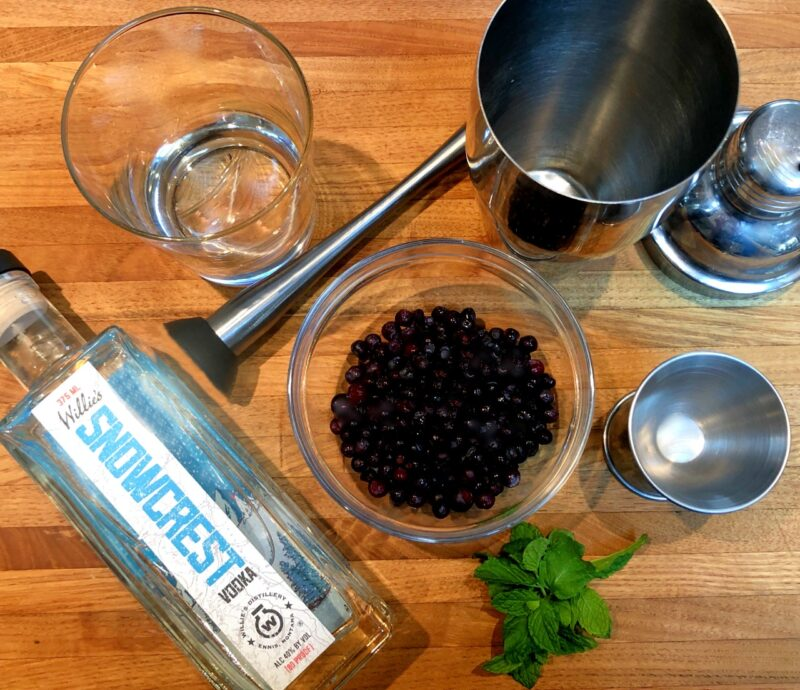 ingredients for a huckleberry cocktail on a wood cutting board