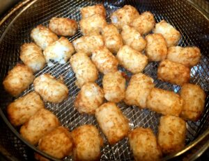 tater tots in air fryer basket after cooking
