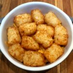 tater tots in oven-safe dish with second layer of tots