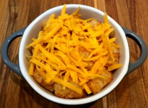 tater tots in oven-safe dish with second layer of tots and cheese