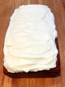 frosted pumpkin bread on a cutting board