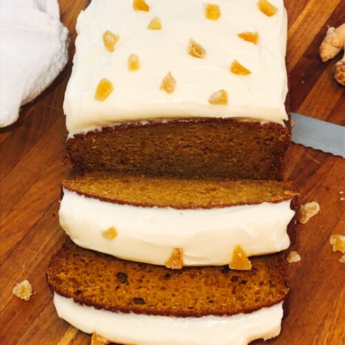 sliced pumpkin bread with icing on a cutting board