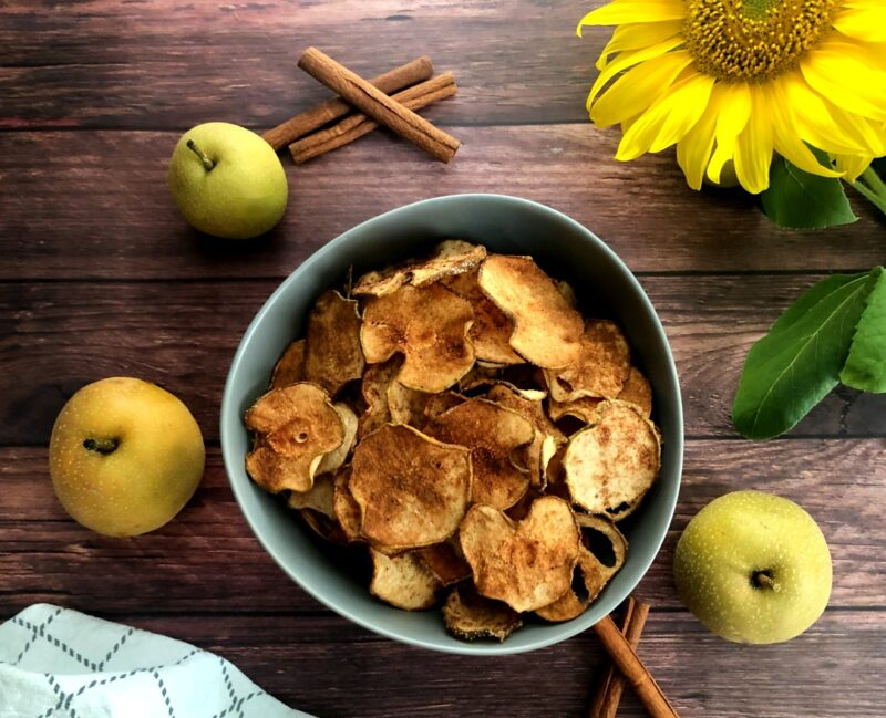 asian pear chips in a bowl and fresh pears and cinnamon sticks
