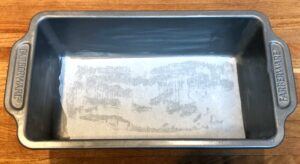 bread pan with butter and parchment paper
