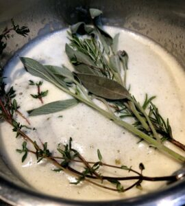 herbs in butter in saucepan