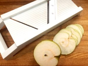 sliced asian pears with mandolin on a cutting board