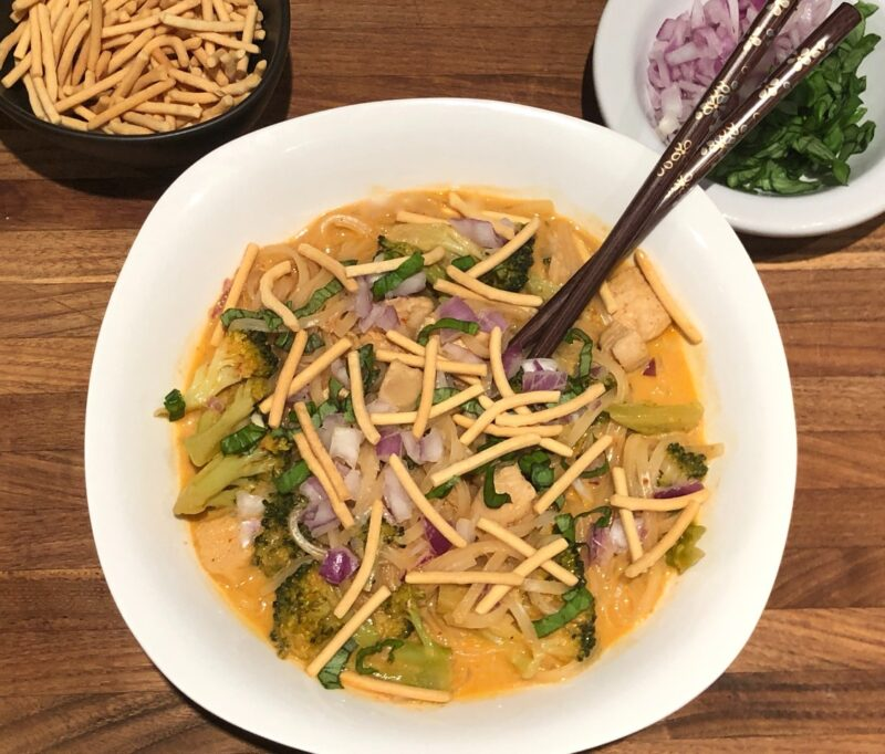 thai red curry soup with noodles and chow mein, basil, and red onion on top