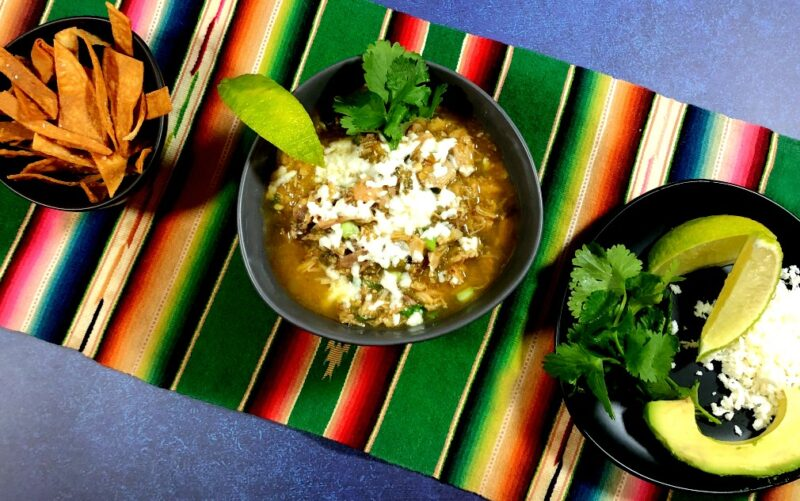 green chicken chile verde with fried tortilla strips, avocado, cilantro and cheese on the side