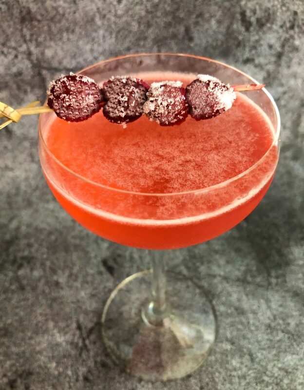 cranberry cocktail with boozy sugared cranberry garnish