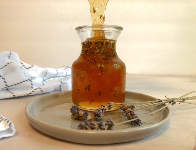 lavender honey in a jar with dried lavender sprigs on the side