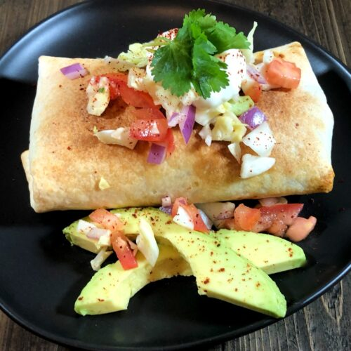air fryer chimichanga with sour cream, avocado, lettuce, tomato and onion on top