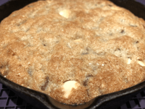 baked gluten free chocolate chip cookie in a mini cast-iron pan