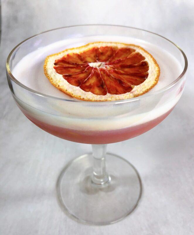 blood orange cocktail with an orange garnish