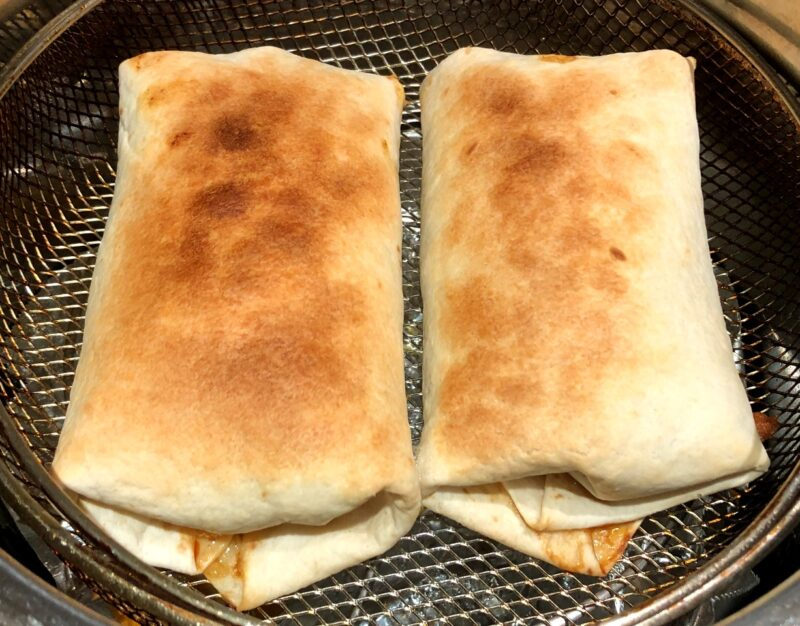 chimichangas in air fryer basket after air frying