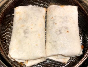 chimichangas on air fryer basket before cooking