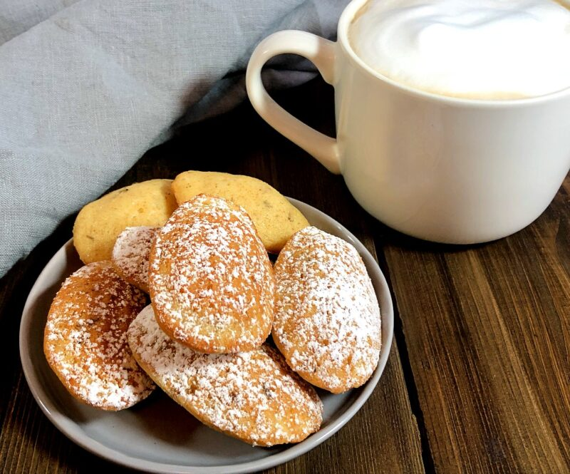 lavender madeleines on a plate and a latte