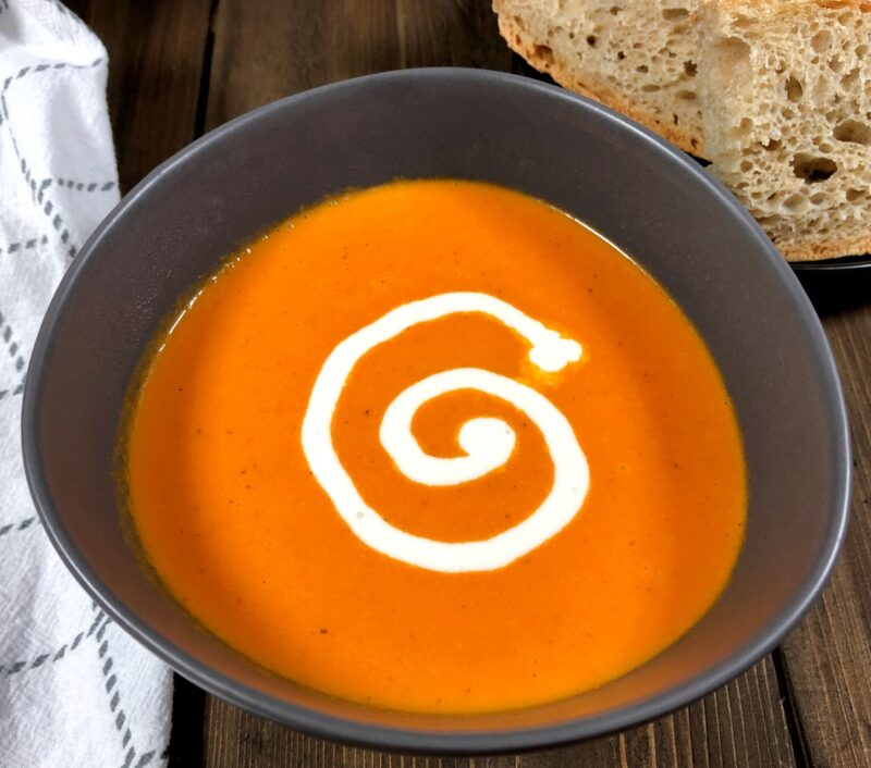 orange tomato soup with bread on the side
