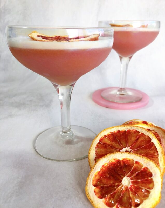 pisco sour cocktails with blood oranges for garnish