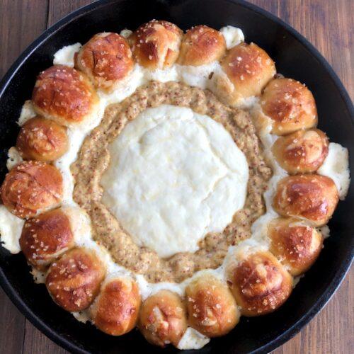 pretzel rolls around a cheese and mustard dip in a skillet