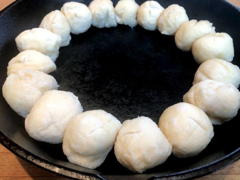 raw pretzel rolls in a cast-iron skillet