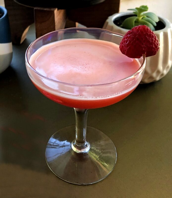 strawberry gin cocktail in a coupe glass with a strawberry garnish